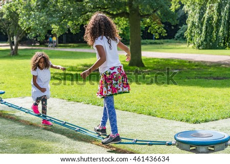 Adorable kids playing outside in park on a summer day. Two brazilian girls with long curly hair wearing a white and colorful dress balancing on a playground, image for family blog