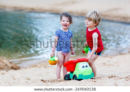Adorable kids, two siblings, girl and boy having fun and playing together with sand toys near city lake on hot summer day. Active outdoors leisure with kids in summer, on sunny ay. - stock photo