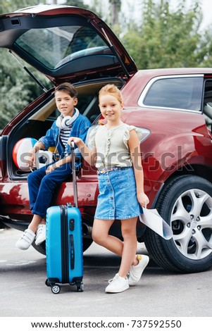 adorable kids with luggage standing next to car before trip