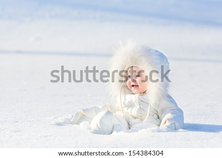 Adorable laughing baby girl in a warm white snow suit playing in snow on a very sunny and clear winter day in a park - stock photo