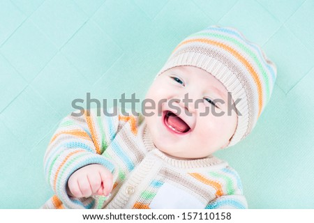 Adorable laughing baby wearing a warm knitted jacket and hat relaxing on a green blanket - stock photo