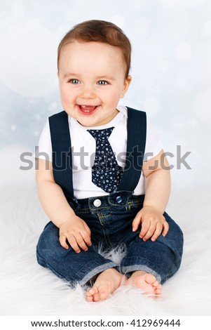 Adorable laughing baby with braces and tie