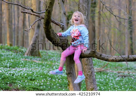 Adorable laughing child, blonde healthy toddler girl enjoying nature, playing, hiking and hiding behind the trees in spring forest with wild anemones flowers - stock photo