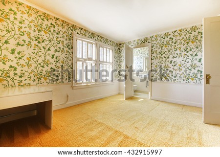 Adorable light bedroom with floral patterned wall paper and carpet connected with bathroom.