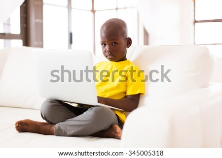 adorable little african american boy using laptop computer at home