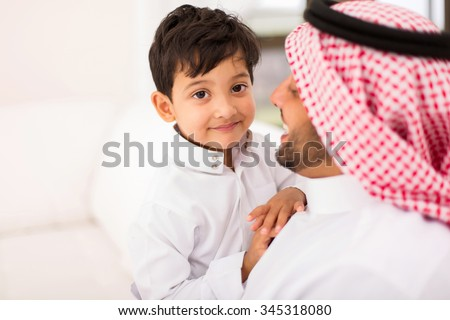 adorable little Arabian boy and his father relaxing at home - stock photo