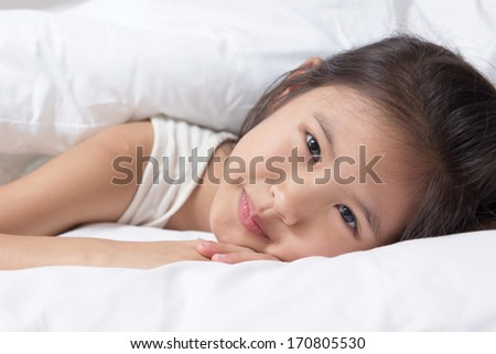 Adorable little Asian girl awaked up in her bed