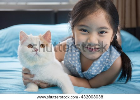Adorable little Asian girl holding her Scottish fold kitten on the bed