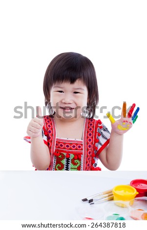 Adorable little asian (thai) girl painting her palm, colorful left hand painted with smiling faces, right hand showing thumb up, happy childhood. Isolated on white background, studio shot - stock photo