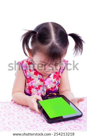 Adorable little asian (thai) girl using digital tablet at desk, tablet pc with blank green screen, isolated on white background, shot in studio - stock photo