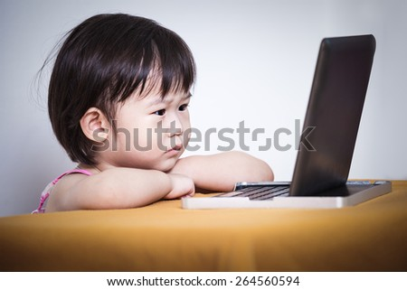 Adorable little asian (thai) girl watching a story on touchscreen tablet computer, concept about education and learning, studio shot - stock photo