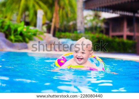 Adorable little baby boy having fun in a swimming pool in a beautiful tropical resort learning to swim playing with colorful inflatable ring - stock photo