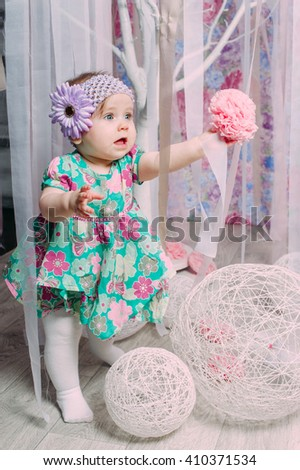 Adorable little baby girl laughing, smiling, creeping & playing in the studio wearing mint dress - stock photo