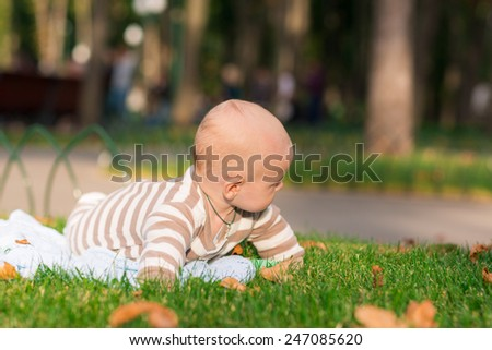 Adorable little baby lying in the park in a cute hat - stock photo