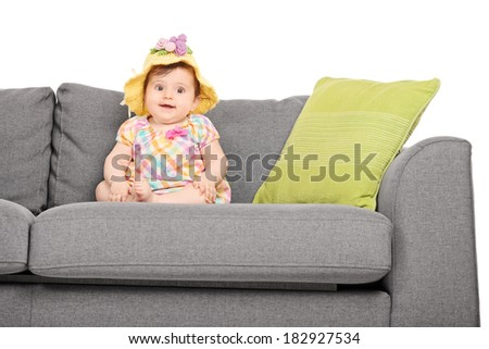 Adorable little baby seated on a couch isolated on white background - stock photo