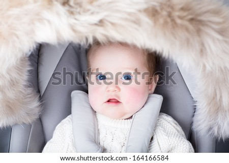 Adorable little baby sitting in a warm stroller - stock photo