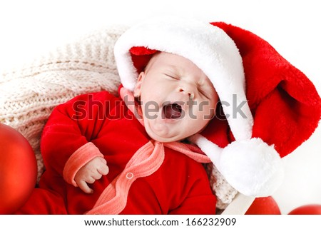 Adorable little baby wearing a santa claus suit and hat lying in straw basket