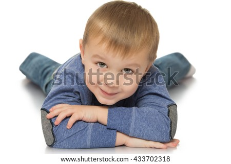 Adorable little blond boy lying on the floor with his head resting on hands - Isolated on white background