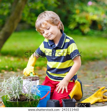 Adorable little blond boy of 3 or 4 years gardening and planting flowers in home's garden or farm, on warm sunny day. Outdoors. Environment concept. - stock photo