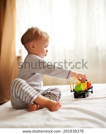 Adorable little blond boy playing with car at home. - stock photo