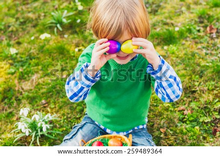 Adorable little blond boy playing with colorful easter eggs in the park - stock photo