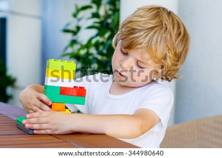 Adorable little blond child playing with lots of colorful plastic blocks indoor. Active kid boy having fun with building and creating. - stock photo