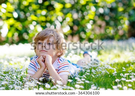 Adorable little blond child with blue eyes laying on the grass with daisies flowers in the park. On warm summer day during school holidays. Kid boy dreaming and smiling. - stock photo