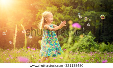 Adorable little blond girl having fun playing with soap bubbles during sunny summer afternoon - stock photo
