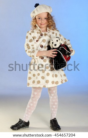 Adorable little blond girl standing at full height and holds handbag with a plush toy. Beautiful child with curly hair playing with toy puppy. - stock photo