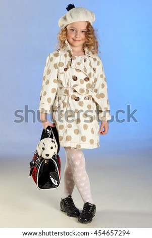 Adorable little blond girl standing at full height and holds handbag with a plush toy. The child stands as a beautiful fashion model. - stock photo
