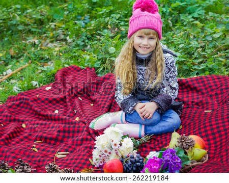 Adorable little blond girl with long blond hair in autumn park. Beautiful little young baby in a pink hat. Beautiful child sitting on a red plaid. - stock photo