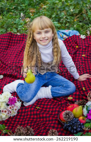 Adorable little blond girl with long blond hair in autumn park. Beautiful little young baby in a pink hat with pear in hand. Beautiful child sitting on a red plaid.  - stock photo
