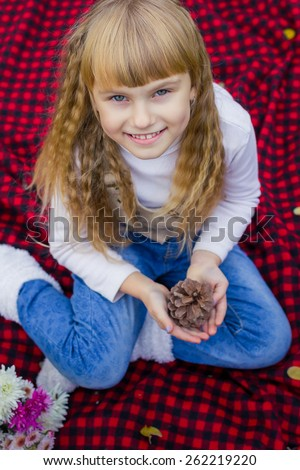 Adorable little blond girl with long blond hair in autumn park. Beautiful little young baby in a pink hat with a lump in his hands. Beautiful child sitting on a red plaid.  - stock photo