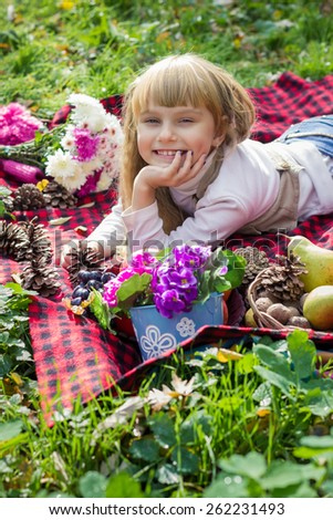 Adorable little blond girl with long blond hair in autumn park. Beautiful little young baby lies on a red plaid.  Lovely child smiling with bright flowers