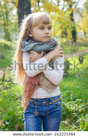 Adorable little blond girl with long blond hair in autumn park. Beautiful little young baby stands in a scarf.  Lovely child  - stock photo