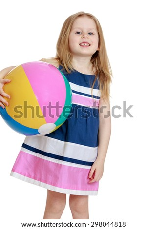 Adorable little blonde girl in summer dress holding under one arm a large beach ball , the girl rests with their parents at the resort next to the sea , she plays ball on the beach-Isolated on white - stock photo