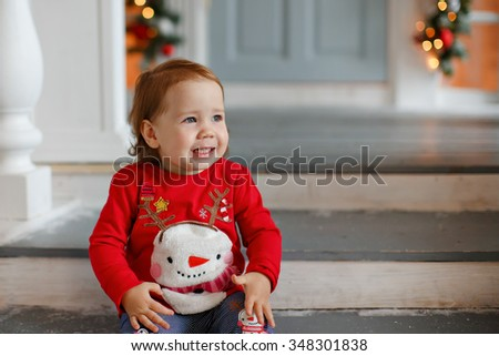 Adorable little blonde girl little girl in a sweater with a snowman sitting on the stair Christmas decorations and a little sad - stock photo