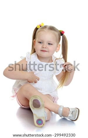 Adorable little blonde girl with her hair braided into pigtails that are tied with colored rubber bands, white shirt and pink shorts is sitting on the floor and looking at the camera-Isolated on white - stock photo