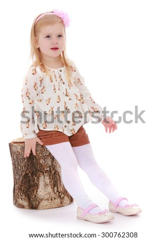 Adorable little blonde girl with her hair which holds a pink rim. The girl is dressed in a white shirt and brown shorts and white tights , and I sat on a birch stump-Isolated on white background - stock photo