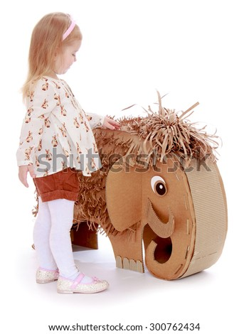 Adorable little blonde girl with her hair which holds a pink rim. The girl is dressed in a white shirt and brown shorts and white tights , girl Stoke elephant out of cardboard-Isolated on white - stock photo