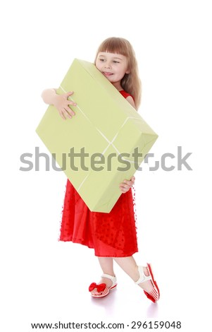 Adorable little blonde girl with long hair in a long red dress holding a large Packed in brown paper carton - isolated on white background - stock photo