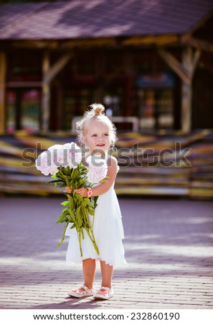 Adorable little blonde girl with peonies in hand against a wooden house - stock photo
