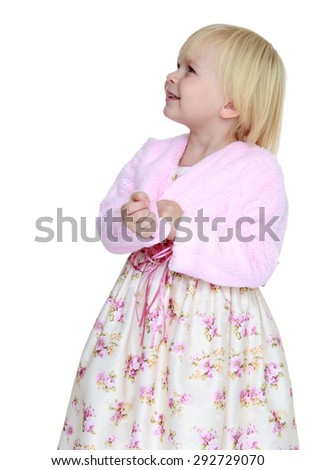 Adorable little blonde girl with short hair in lush elegant dress and a pink jacket looks in tops , close-up - isolated on white background - stock photo