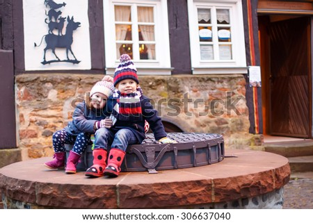 Adorable little boy and girl, siblings on  Christmas funfair or market, outdoors. Happy children, friends having fun. Selective focus on one child. Holiday, children, lifestyle concept. - stock photo