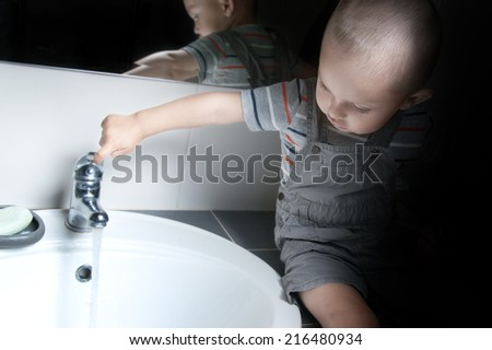 Adorable  little boy at the age of two in a striped T-shirt  looking at the flow of water in the sink - stock photo
