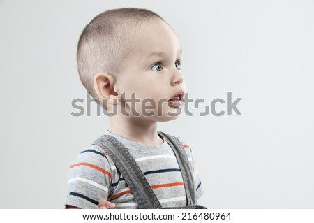Adorable  little boy at the age of two in a striped T-shirt on a light gray background - stock photo