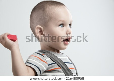 Adorable  little boy at the age of two in a striped T-shirt throws a cube on a light gray background - stock photo
