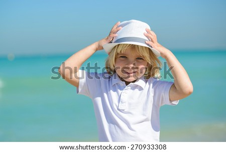 Adorable little boy  at the beach during summer vacation - stock photo