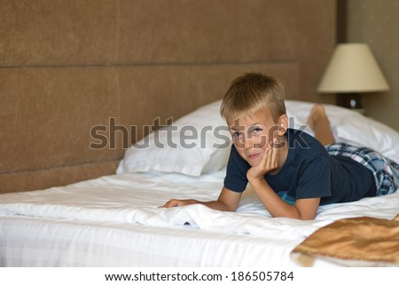 Adorable little boy awaked up in her bed - stock photo