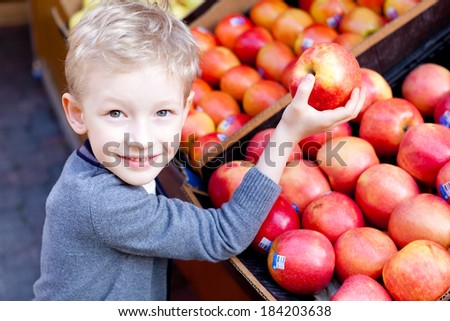 adorable little boy choosing fruits at the marker - stock photo